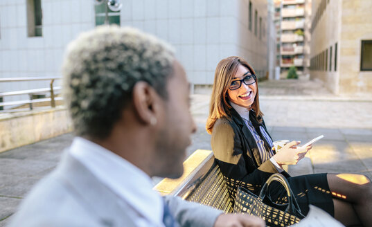 Young businessman and woman sitting on bench, talking - DAPF00647