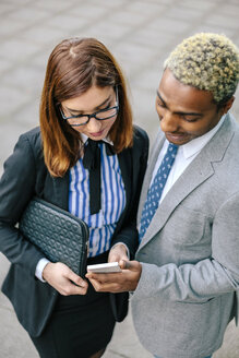 Young businessman and woman looking at smart phone - DAPF00653