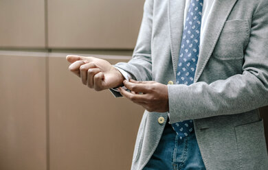Businessman adjusting cuffs, close up - DAPF00662