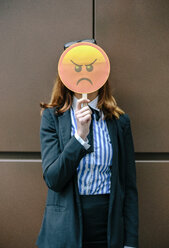 Woman hiding face behind emoji mask - DAPF00671
