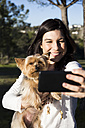 Happy young woman taking selfie with her dog - ABZF01944