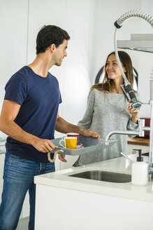 Young couple with coffee cups on tray in kitchen - SIPF01543