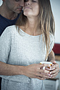 Young man embracing girlfriend holding coffee cup - SIPF01546