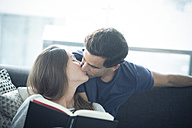 Young man kissing girlfriend with book at home - SIPF01552