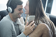 Happy young couple with headphones and smartphone at home - SIPF01561