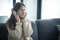 Smiling young woman listening to music at home - SIPF01564