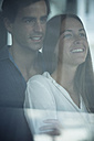 Smiling young couple looking out of window - SIPF01573