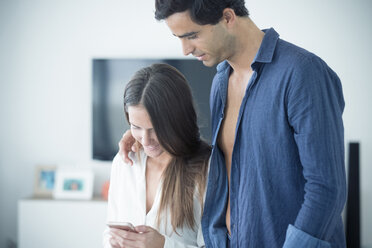 Young couple in love looking at cell phone at home - SIPF01576
