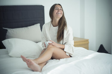 Happy young woman sitting on bed with cup of coffee - SIPF01585