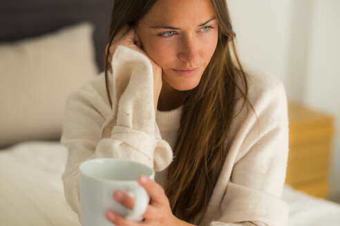 Young woman sitting on bed with cup of coffee - SIPF01588