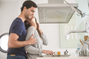 Happy young couple in love with coffee cups in kitchen - SIPF01600