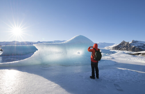 Iceland, tourist taking cell phone picture of glacial ice - RAEF01796