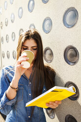 Young woman with coffee to go reading book - VABF01295