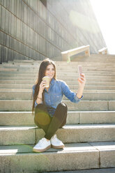 Young woman with coffee to go sitting on stairs taking selfie with smartphone - VABF01298