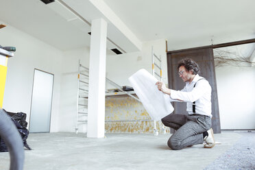 Architect with construction plan at construction site - REAF00245