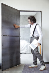 Architect checking steel door at construction site - REAF00251
