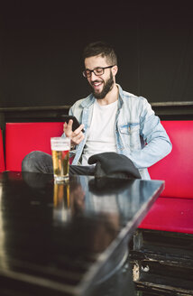 Smiling young man sitting in a pub reading messages on smartphone - RAEF01810