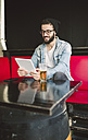 Smiling young man sitting in a pub using tablet - RAEF01816