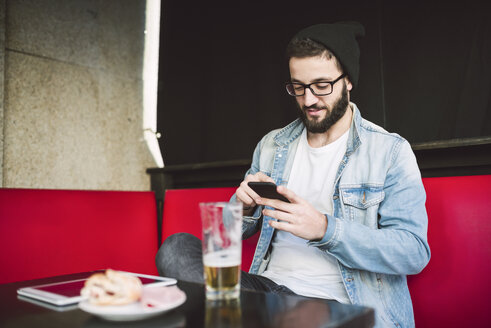 Young man sitting in a pub checking messages - RAEF01819