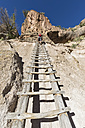 USA, New Mexico, Frijoles Canyon, Bandelier National Monument, Ruins and reconstructed kiva of the Ancestral Pueblo People, tourist on ladder towards Alcove House - FOF09171