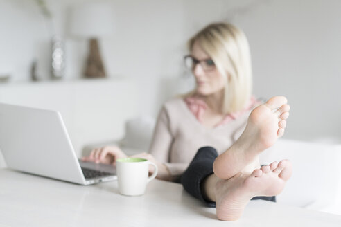Woman sitting at table with feet up using laptop - CHPF00380