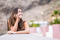 Portrait of smiling woman with leaning on a wall - SIPF01613