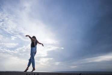 Woman with arms outstretched balancing on wall in front of sky - SIPF01616