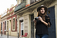 Portrait of smiling young woman with camera outdoors - KKAF00643