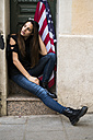 Portrait of young woman sitting at house entrance with US American flag - KKAF00646