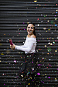 Happy young woman standing in front of black roller shutter throwing confetti - KKAF00658