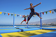 Playful mother and son bouncing on trampoline at the coast - SIPF01624
