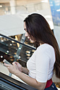 Woman using a smartphone in a shopping mall - MOMF00045
