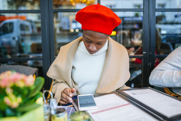 Young woman in Paris reading text messages in a cafe - KIJF01371