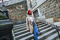 Young woman in Paris walking on stairs - KIJF01374