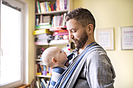 Father with baby son in sling at home - HAPF01409