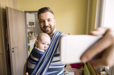 Father with baby son in sling at home taking a selfie - HAPF01418