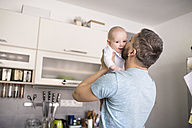 Father holding and kissing baby son in kitchen - HAPF01439