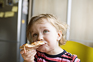 Little girl at home eating slice of pizza - HAPF01445