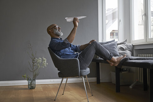 Mature man plying with paper plane - FMKF03739