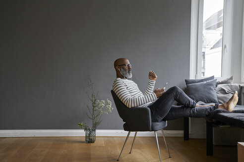 Mature man sitting with feet up, using smartphone - FMKF03745