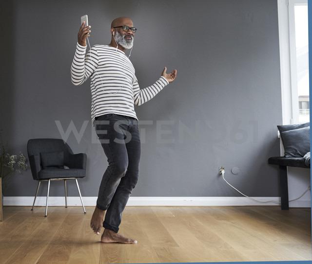 Mature man dancing alone at home, holding smart phone - FMKF03751