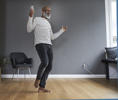 Mature man dancing alone at home, holding smart phone - FMKF03751