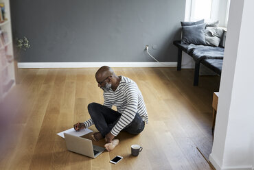 Mature man sitting on floor, working on laptop - FMKF03757