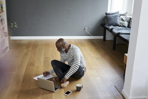 Mature man sitting on floor, working on laptop - FMKF03757