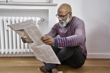 Mature man sitting on thefloor, reading newspaper - FMKF03766