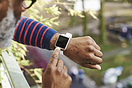 man looking at smartwatch - FMKF03778