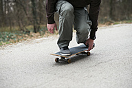 Close-up of man skating down the road - MOMF00046