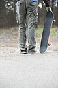 Close-up of man standing and holding skateboard - MOMF00049