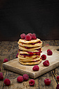 Stack of pancakes with raspberries and raspberry jam on wooden board - LVF06016