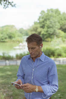 Man with smartphone and earphones in a park - BOYF00756